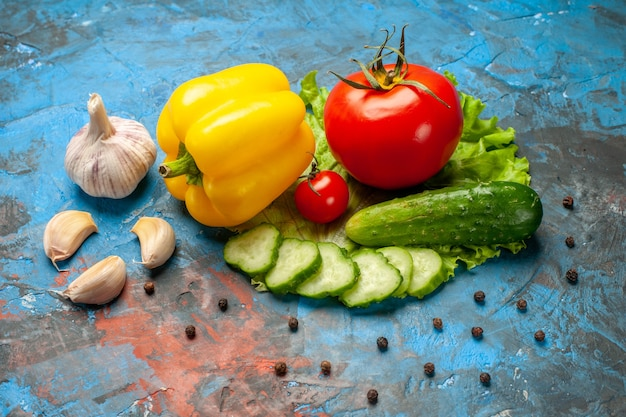 Front view fresh vegetables cucumber tomato green salad and garlic on blue background meal salad health ripe food color
