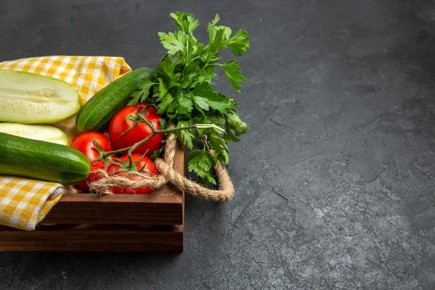 Вид спереди свежие овощи красные помидоры, огурцы и кабачки с зеленью на сером пространстве