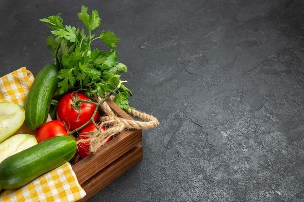 Vista frontale verdure fresche pomodori rossi cetrioli e zucche con verdure sullo spazio grigio