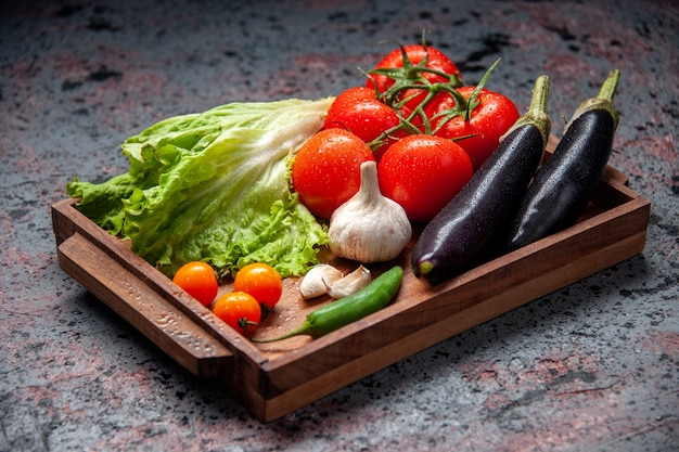 Front view fresh vegetables red tomatoes garlic green salad and eggplants inside wooden board on blue background