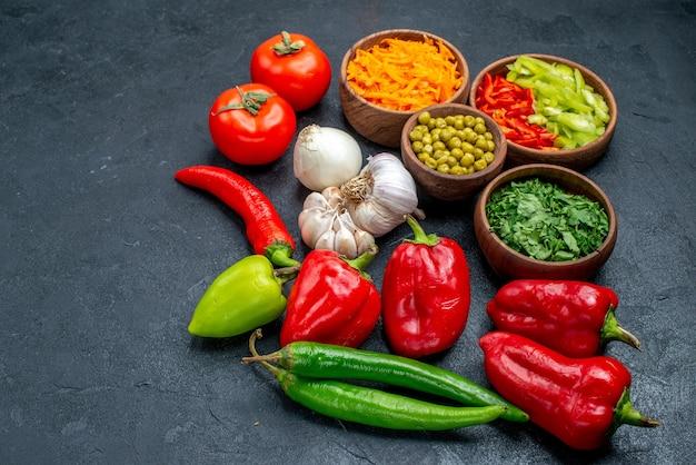 어두운 테이블에 잘 익은 샐러드 야채에 마늘과 콩을 곁들인 신선한 야채 전면 보기