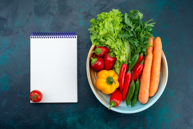Вид спереди свежие овощи с зеленью и блокнот на синем столе закуска обед салат овощная еда