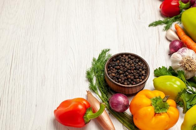 白い机の上の緑と新鮮な野菜の正面図熟したサラダ健康野菜