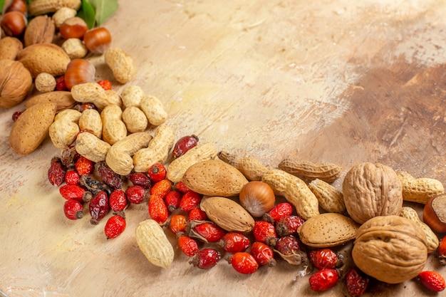 正面図木製の机の上のピーナッツと新鮮なクルミナッツクルミの写真