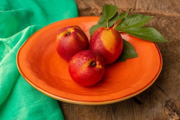 正面の木製の机の上のオレンジ色のプレート内の新鮮な桃全体