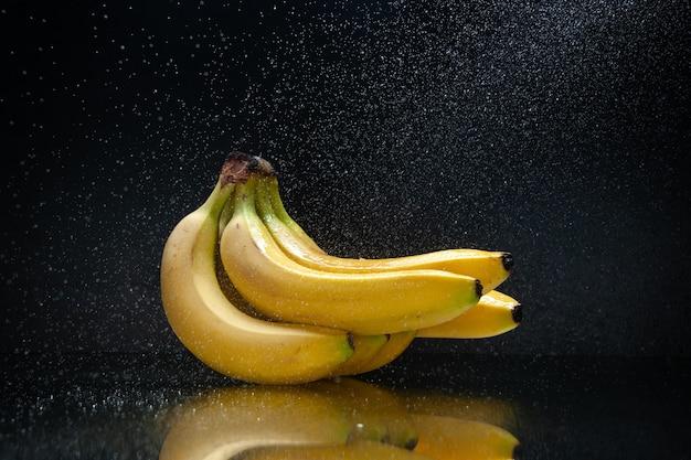 暗い背景のフルーツトロピカルエキゾチックな色の暗闇の正面図新鮮な黄色のバナナ