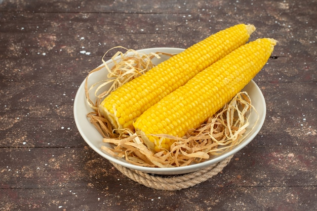 Front view fresh yellow corns inside white plate on wood, food meal raw color