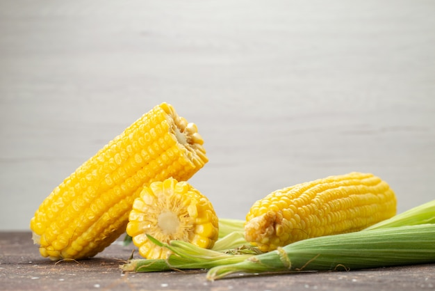 Front view fresh yellow corns with peels on grey, food meal color
