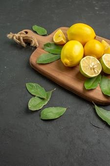 正面図暗い背景に新鮮な黄色のレモン酸っぱい果物