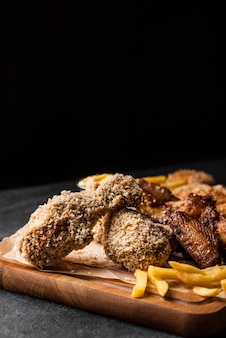 Front view of fried chicken legs with french fries and copy space