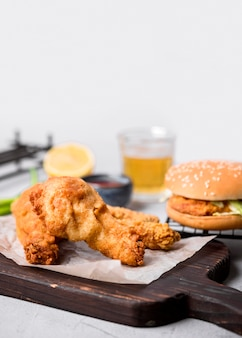 Жареный цыпленок на разделочной доске с гамбургером, вид спереди