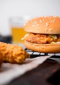 Жареные кусочки курицы и гамбургер на подносе, вид спереди