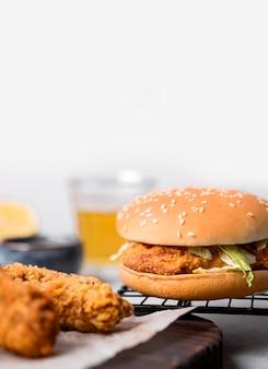 Жареные кусочки курицы и гамбургер, вид спереди