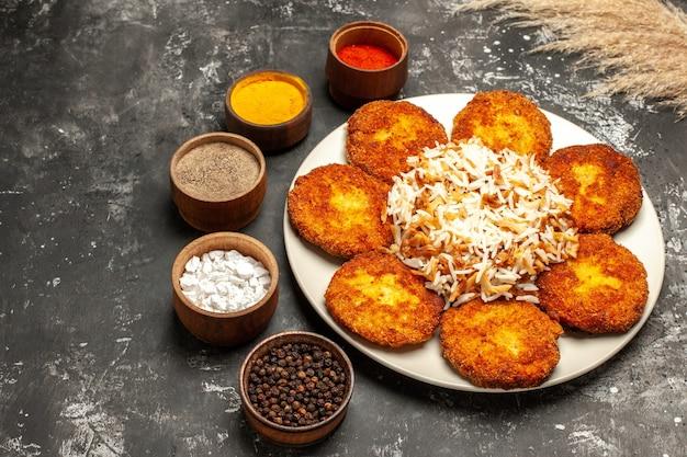 Вид спереди жареные котлеты с вареным рисом и приправами на темной поверхности блюдо фото мясо