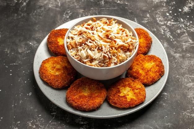 Vista frontale cotolette fritte con riso cotto su carne di polpetta piatto superficie scura