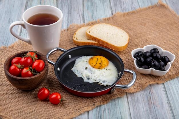Vista frontale dell'uovo fritto in padella con ciotola di pomodoro e tè con fette di pane e ciotola di oliva su tela di sacco e superficie di legno