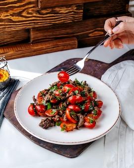 正面の赤肉と豆、茶色の木製の机と表面の白いプレート内の豆と一緒に揚げた肉