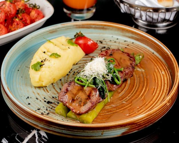 Вид спереди жареного мяса на спарже с картофельным пюре и зеленью в тарелке