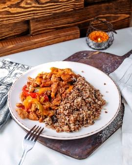 Вид спереди жареных кусочков мяса вместе с гречкой внутри белой тарелки на коричневом деревянном столе и поверхности