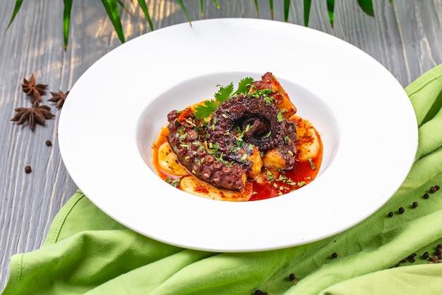 Вид спереди жареного осьминога в соусе с картофелем