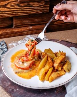 茶色の床に白い皿の中の野菜と一緒にフライドポテトの正面図