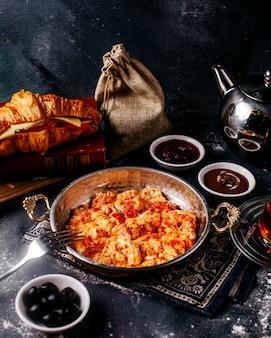 La vista frontale ha fritto le uova di pomodori saporite con il pane e il tè delle olive sul pavimento grigio