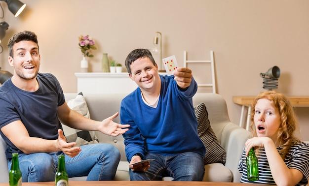 Vista frontale di carte da gioco degli amici a casa e che mangiano birra