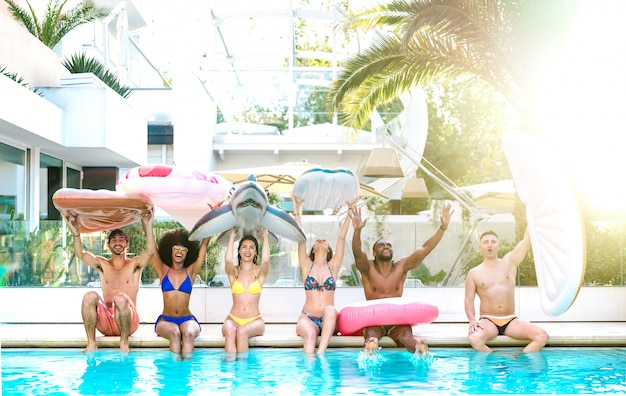 Front view of friends sitting at pool party with lilo airbed and swim wear - bright filter