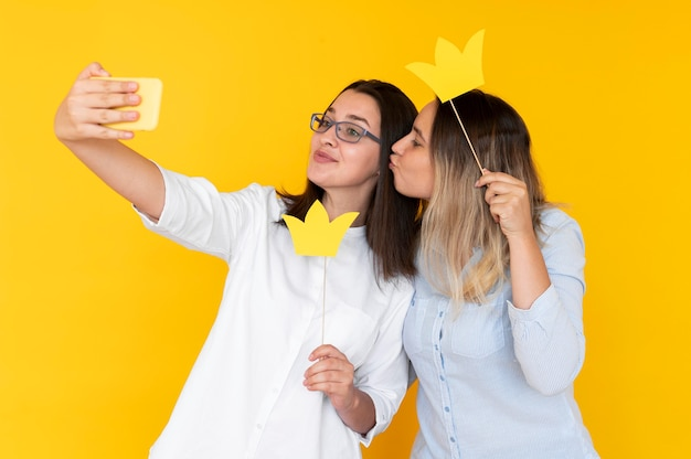 Front view of friends taking selfies with crown