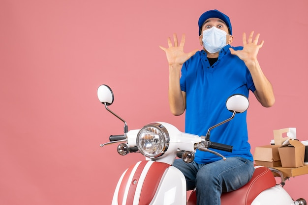 Front view of frigthened delivery guy in medical mask wearing hat sitting on scooter on pastel peach background