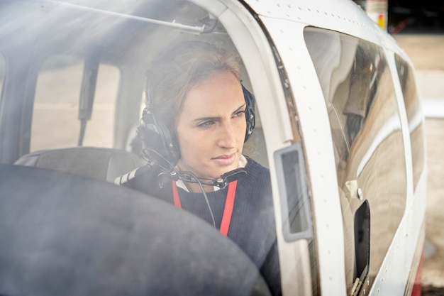 Front view from outside of a female pilot in the cockpit of an airplane