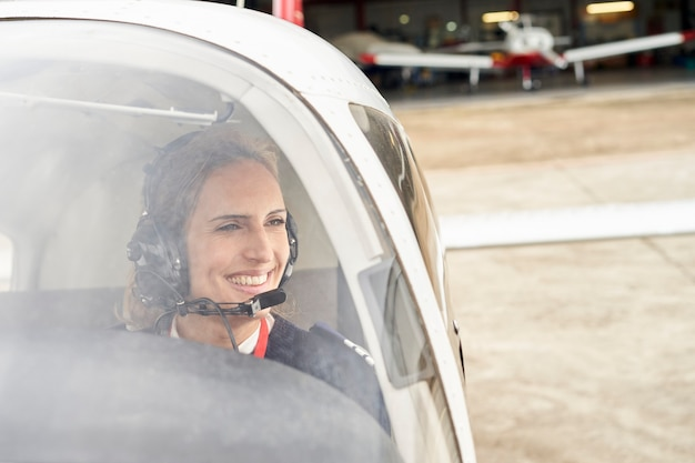 Front view from outside of a smiling female pilot in the cockpit of an airplane