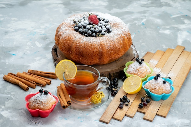 A front view fruit cake delicious and round formed with fresh blue,berries and along with cup of tea on bright, cake biscuit sweet sugar