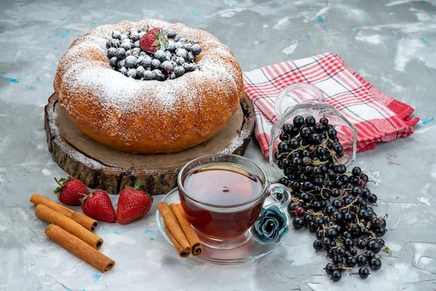 Una torta di frutta vista frontale con blu fresco, frutti di bosco e insieme a una tazza di tè su zucchero dolce dolce e luminoso