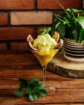 Un cocktail di frutta di vista frontale con ghiaccio sul cocktail della spremuta della bevanda della frutta dello scrittorio di legno marrone