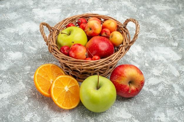 Вид спереди фруктовая композиция, разные свежие фрукты внутри корзины на белом пространстве