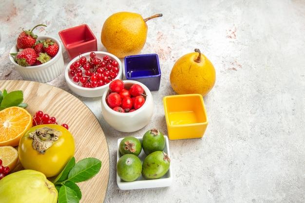 Vista frontale composizione di frutta frutti diversi sul tavolo bianco frutti di bosco freschi maturi colore