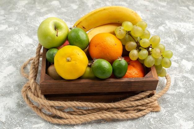 Vista frontale composizione di frutta uva mandarini e feijoa su sfondo bianco frutta matura vitamina dolce fresco