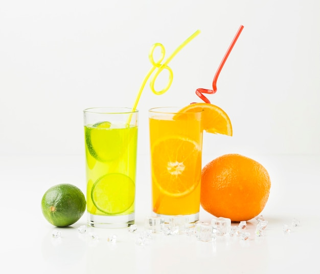 Front view of fruit juice in glasses with straws