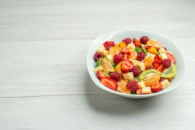 正面図フルーツサラダスライスしたキウイタンジェリンイチゴとリンゴ白い表面の木の色まろやかな熟した写真ダイエットフルーティーなテキストの空きスペース
