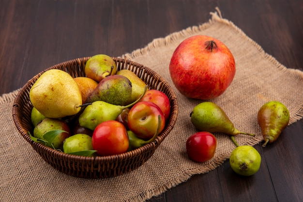 Front view of fruits as peach apple plum in basket with pomegranate on sackcloth on wooden surface