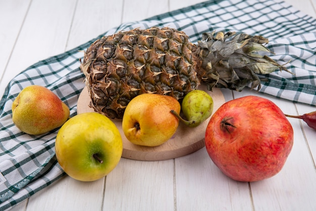 Front view of fruits as pineapple peach on cutting board on plaid cloth with pomegranate apple on wooden surface