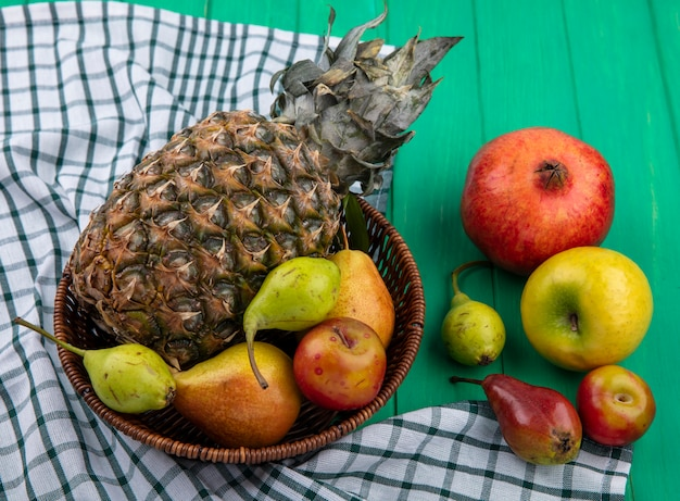 Front view of fruits as pineapple peach plum in basket on plaid cloth with pomegranate apple on green surface