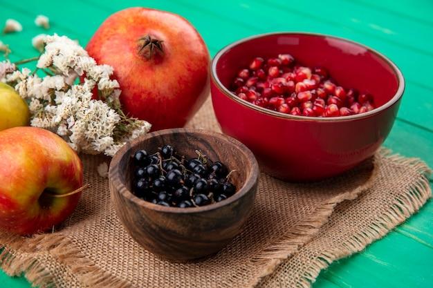 Vista frontale di frutti come melograno e bacche di prugnola in ciotole con fiori su tela di sacco e mele melograno su tela di sacco e superficie verde