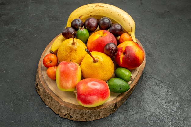 Вид спереди фруктовая композиция свежие фрукты на сером цвете стола спелые много свежих