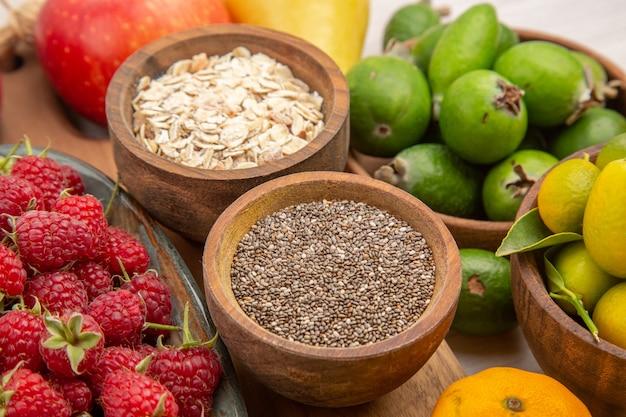 白い机の上の果物の組成の正面図熱帯の熟した色エキゾチックなまろやかなダイエット写真