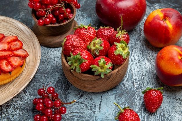Vista frontale della torta fruttata con fragole fresche sulla superficie scura