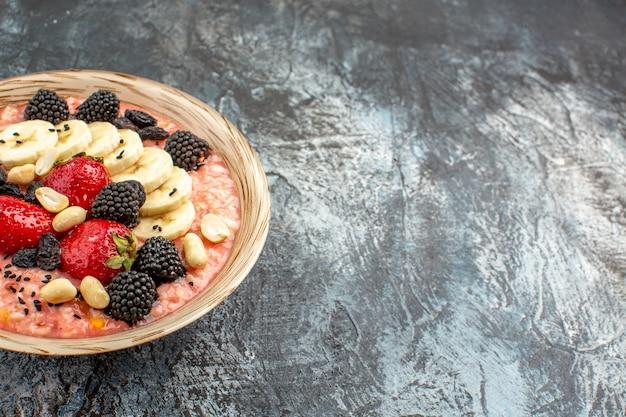 Фруктовые мюсли с нарезанными фруктами на темном столе на завтрак из хлопьев
