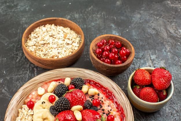 明暗の机の上のスライスされた果物と正面図フルーティーミューズリーシリアル健康フルーツ