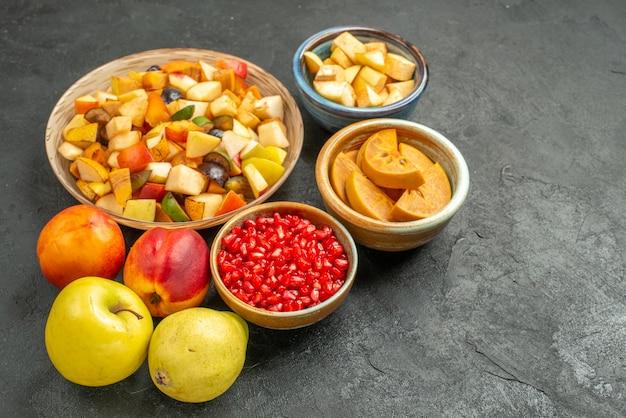 暗いテーブルの上の新鮮なスライスされた果物と正面図フルーティーサラダ多くの果物の健康